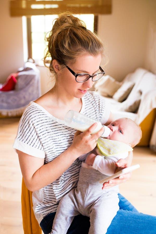 Fils de alimentation de bébé de belle mère, lait dans la bouteille, smartphone photographie stock