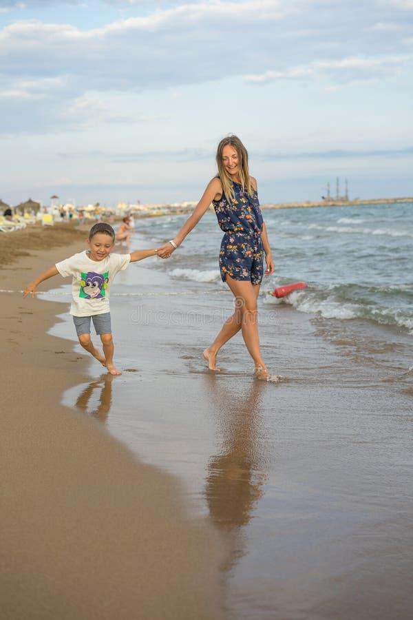 Fils de jeune bébé garçon de mère et de sourire jouant sur la plage sur le coucher du soleil Émotions humaines positives, sentime image stock