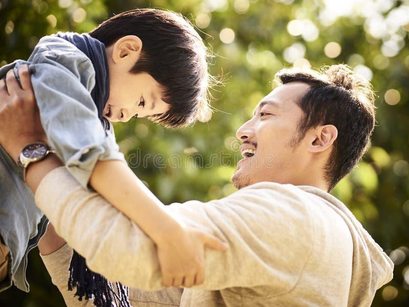 Fils de levage d'enfant de père asiatique dans la joie photos libres de droits