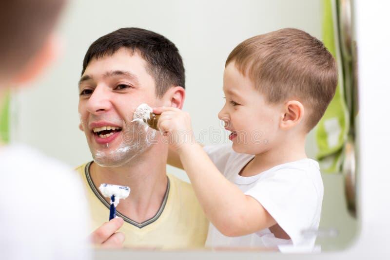 Fils de père et d'enfant rasant ensemble à la maison photographie stock libre de droits