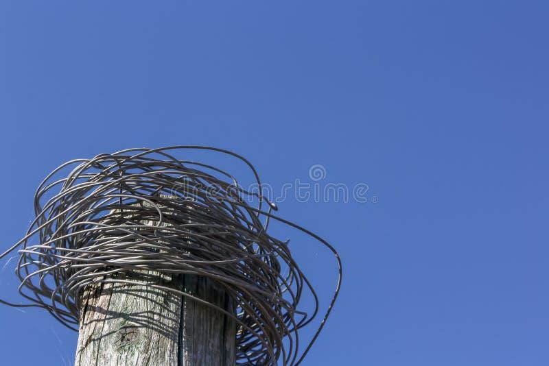 Fils en acier malpropres de puissance sur le poteau électrique en bois abandonné contre le ciel bleu image libre de droits