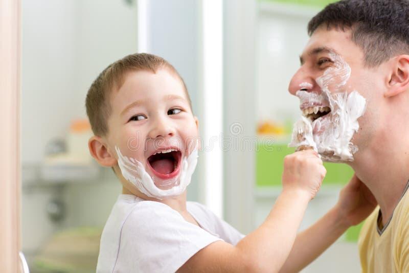 Fils espiègle de père et d'enfant rasant et ayant l'amusement photo libre de droits