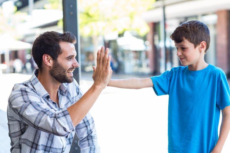 Fils et père faisant la haute cinq photo stock