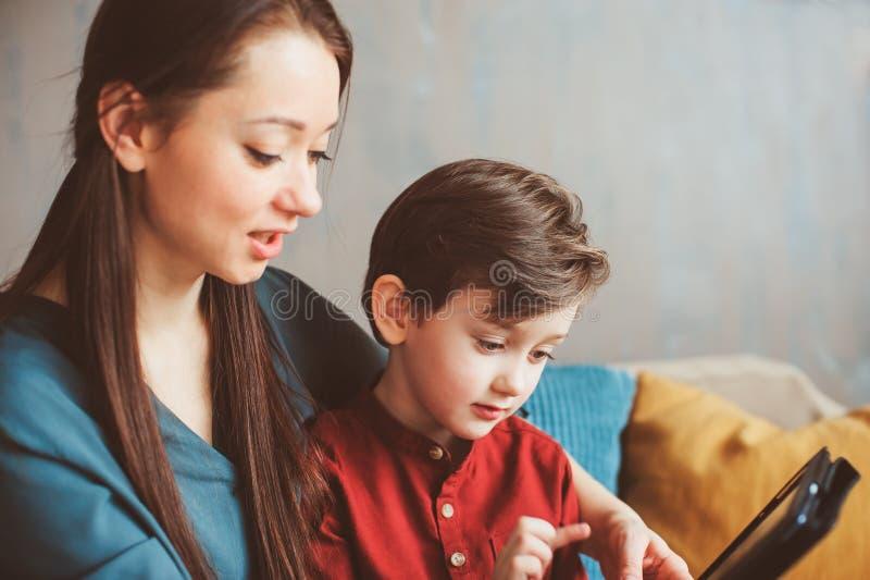 fils heureux de mère et d'enfant en bas âge à l'aide du comprimé à la maison Famille jouant l'ordinateur ou recherchant l'Interne photographie stock