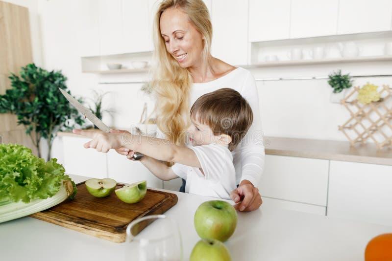 Fils heureux de mère préparant la cuisine saine de maison de petit déjeuner photographie stock libre de droits