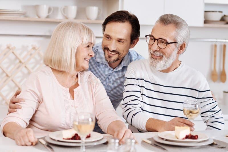 Fils mûr gai étreignant les parents pluss âgé à la maison image libre de droits