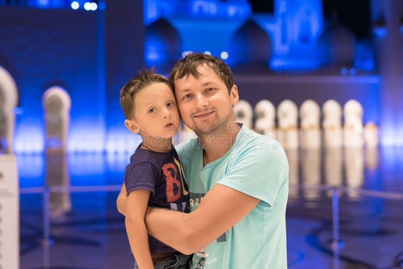Fils mignon et père rêvant à la mosquée grande de Sheikh Zayed Mosque en abaya de port d'Abu Dhabi, paranja dans la nuit Travell image stock