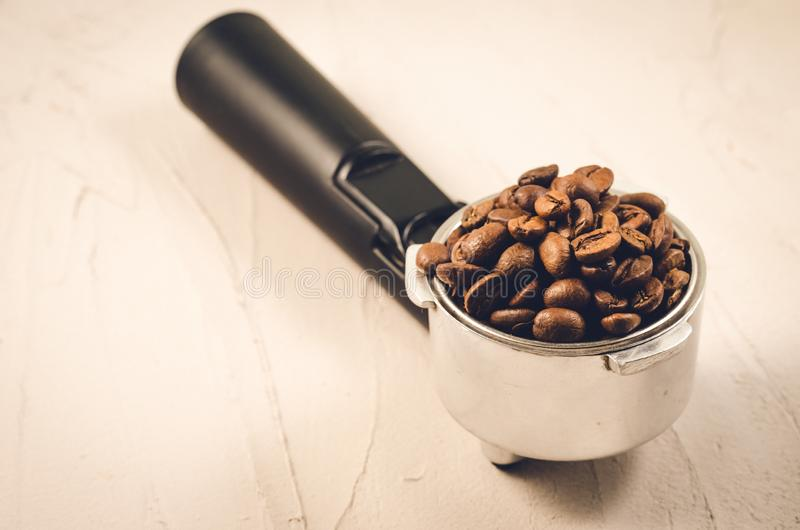 Filter holder and roasted beans coffee/Filter holder and roasted beans coffee on a concrete background. Selective focus and. Filter holder and roasted beans stock images