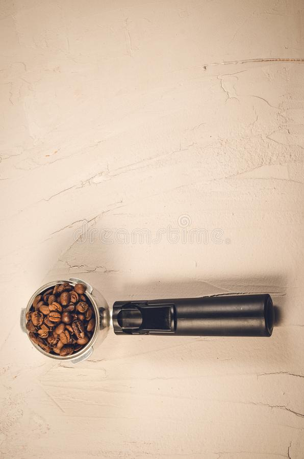 Filter holder and roasted beans coffee/Filter holder and roasted beans coffee on a concrete background. Top view and copyspace. Filter holder and roasted beans royalty free stock image