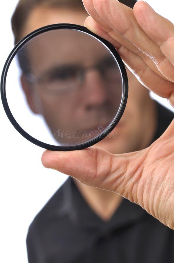 Filter inspection. Closeup of photographer man holding and looking through circular polarizer filter royalty free stock photos