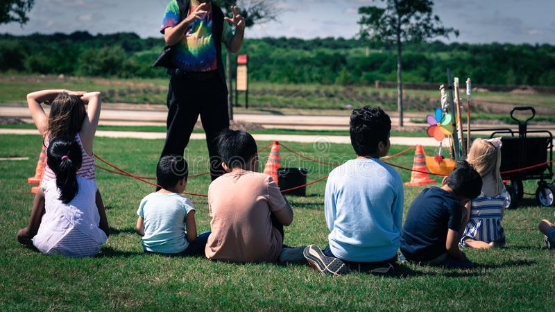 Filtered image close-up rear view multicultural children on grass meadow of outdoor game stock images