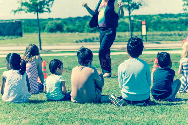Filtered image close-up rear view multicultural children on grass meadow of outdoor game stock photography