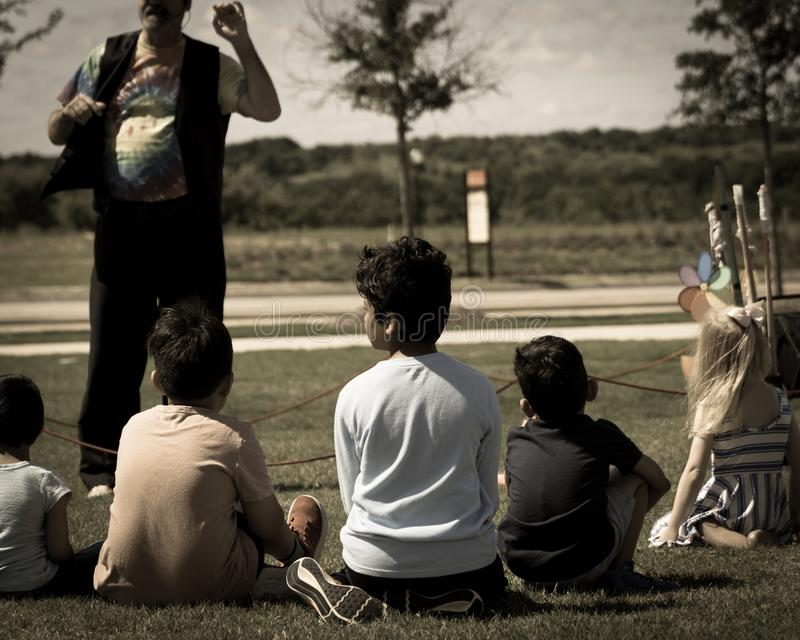 Filtered image close-up rear view multicultural children on grass meadow of outdoor game stock photo