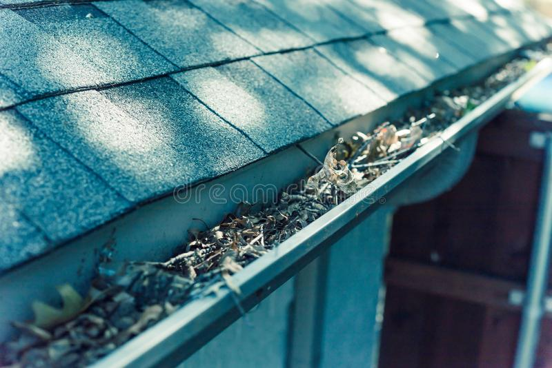 Filtered image gutter clogged by dried leaves and messy dirt need clean-up. Vintage tone gutter near roof shingles of residential house full of dried leaves and royalty free stock photography