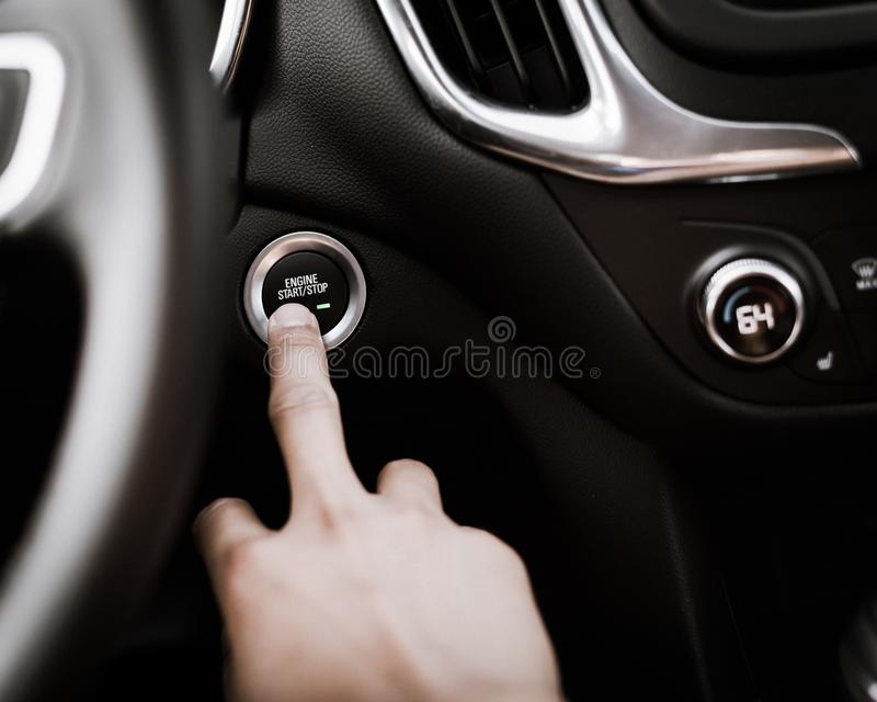 Filtered image hand pressing the start stop button on keyless car stock photography