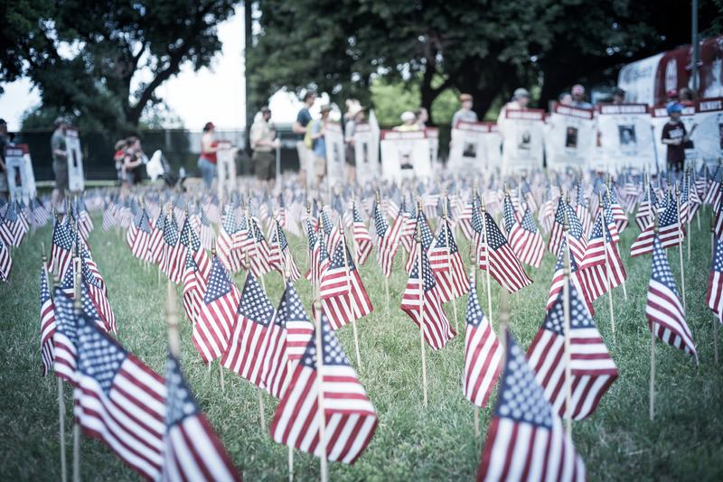 Filtered image lawn American flags with blurry row of people carry fallen soldiers banners parade stock images