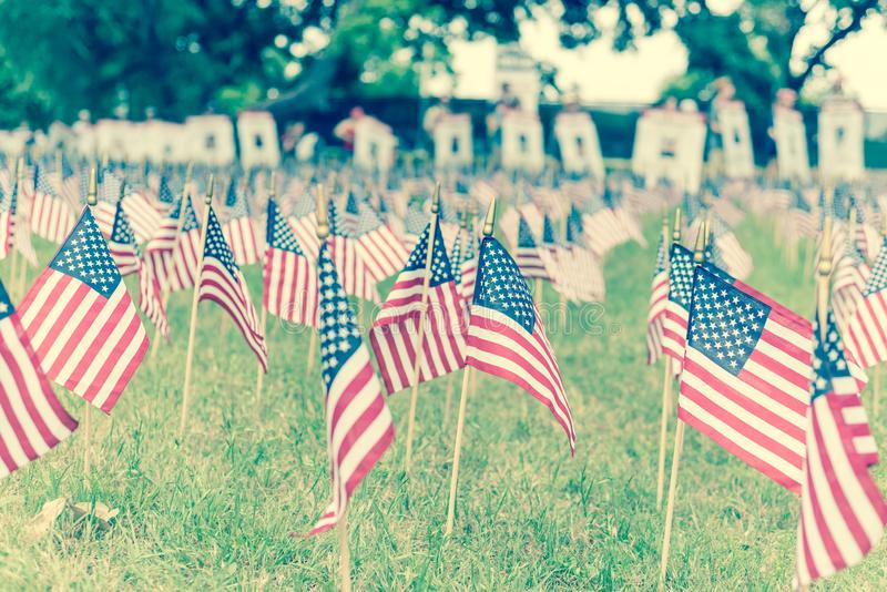 Filtered image lawn American flags with blurry row of people carry fallen soldiers banners parade stock image