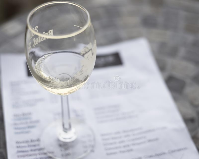 Filtered image wine taste concept with glass of dry white wine and tasting menu. Vintage tone top view a glass of sweet white wine and tasting menu with price at royalty free stock photo