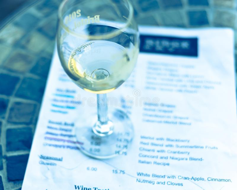 Filtered image wine taste concept with glass of dry white wine and tasting menu. Vintage tone top view a glass of sweet white wine and tasting menu with price at stock photo