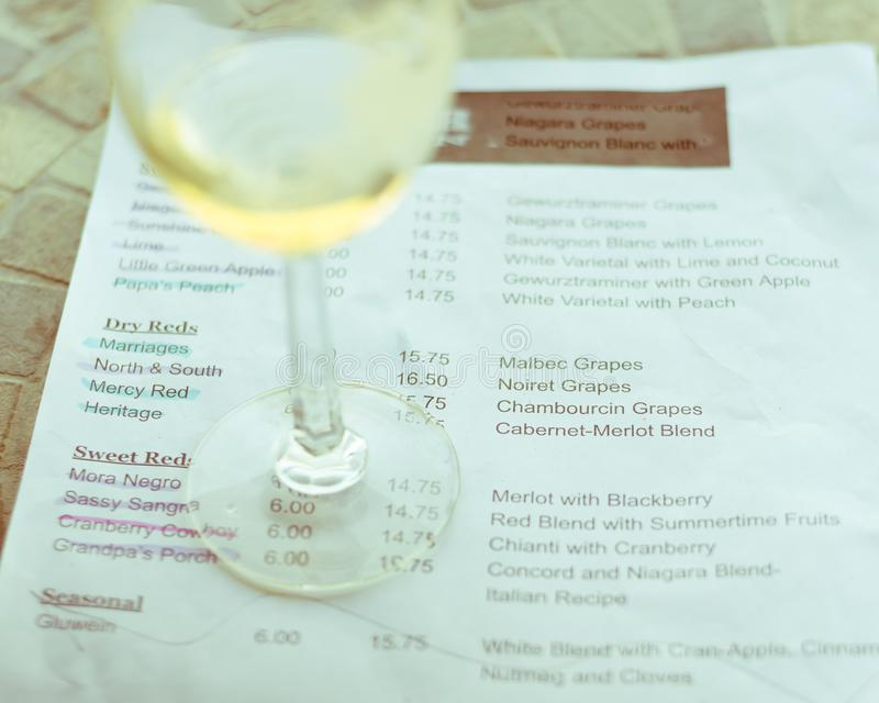 Filtered image wine taste concept with glass of dry white wine and tasting menu. Vintage tone top view a glass of sweet white wine and tasting menu with price at stock image