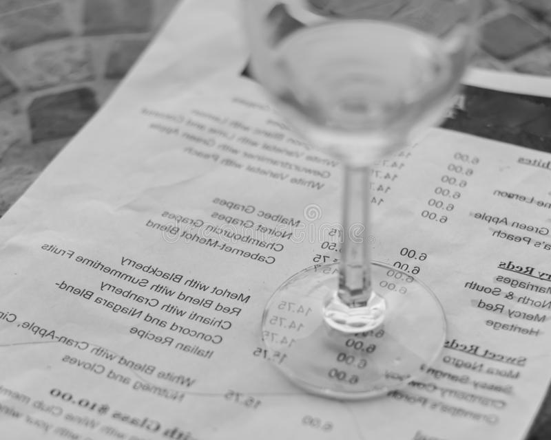 Filtered image wine taste concept with glass of dry white wine and tasting menu. Vintage tone top view a glass of sweet white wine and tasting menu with price at stock images