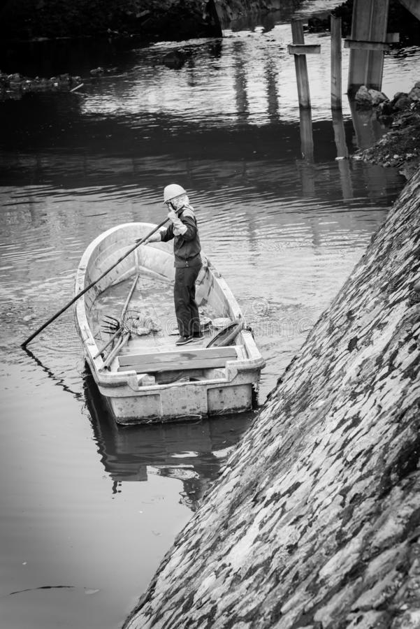 Filtered image woman worker on the boat cleaning up a polluted river in Hanoi, Vietnam stock photo