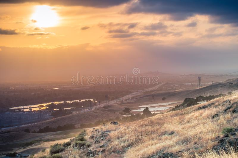 Filtered light shining over the grassy hills of south San Francisco bay area, San Jose; Bayshore Freeway visible in the valley,. California stock images