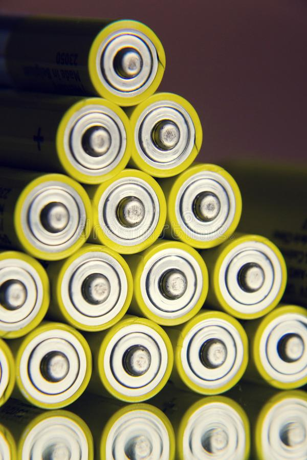 Yellow double A batteries reflecting in mirror, electricity storage concept. Filtered photo - stack of yellow AA batteries reflecting in mirror close up royalty free stock photo