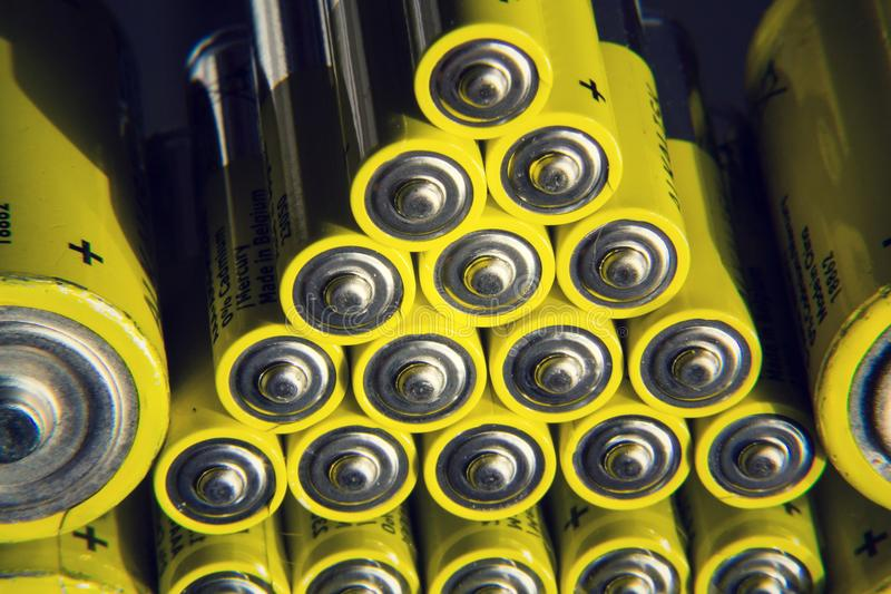 Yellow double A batteries reflecting in mirror, electricity storage concept. Filtered photo - stack of yellow AA batteries reflecting in mirror close up stock photography