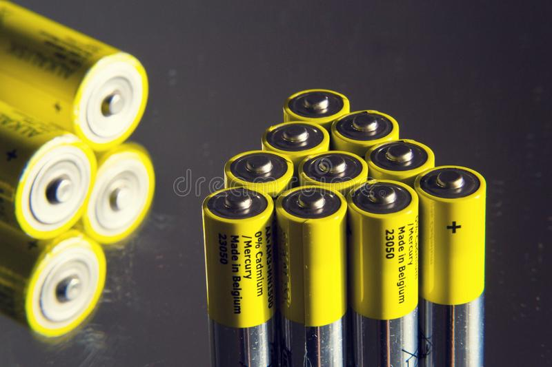 Yellow double A batteries reflecting in mirror, electricity storage concept. Filtered photo - stack of yellow AA batteries reflecting in mirror close up stock photo