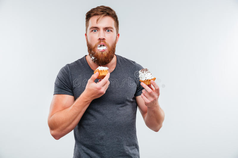Filthy bearded young man eating cream cakes. Isolated on white background royalty free stock images
