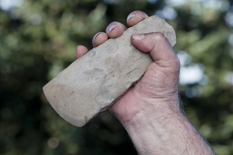 Filthy hand holding handaxe stock photo