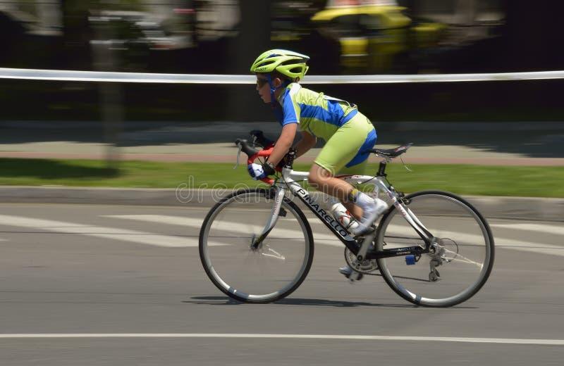 Filtração de uma bicicleta muito nova da equitação do menino em um dia ensolarado, competindo para o evento grande de Prix da est fotografia de stock royalty free