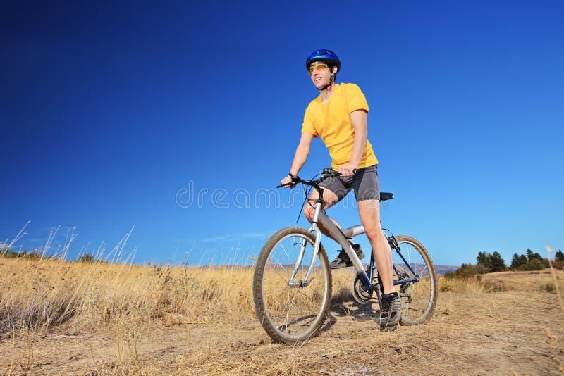 A filtração disparou de um cavaleiro da bicicleta que monta um Mountain bike fora imagem de stock royalty free