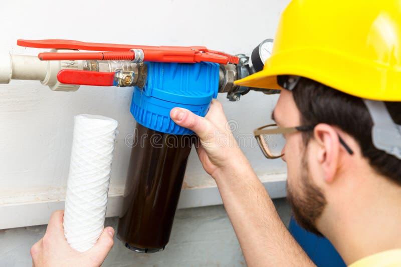 Filtragem da água - filtro de água em mudança do encanador fotografia de stock