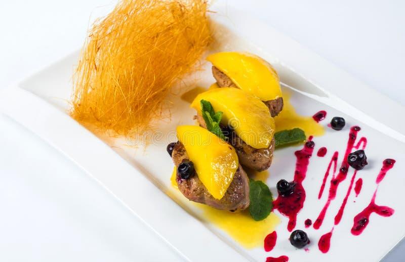 Filtre gras passados ligeiramente do foie na manga e na romã maduras foto de stock royalty free