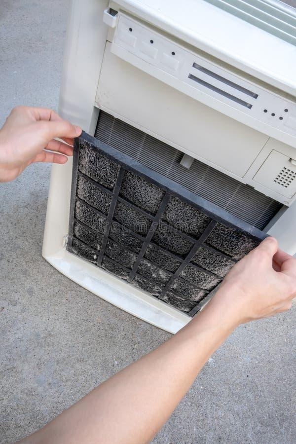Filtre sale de carbone de participation de main de femme de l'épurateur d'air à nettoyer photo stock