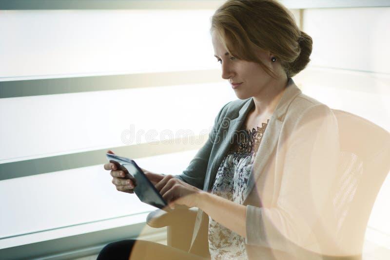 Filtrerad stående av en utövande handstil för affärskvinna på en glasvägg på solnedgången royaltyfria foton