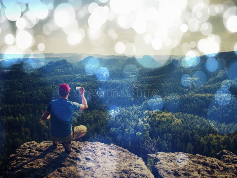 filtrerat Manfotvandraren som sitter på, vaggar i berg fotografering för bildbyråer