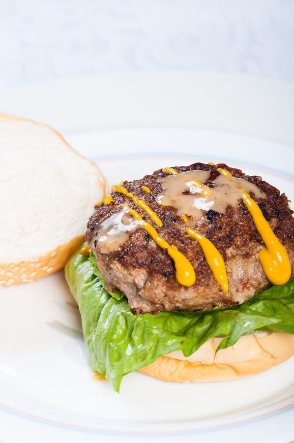 Filtrez l'hamburger frit avec des habillages de moutarde et de sésame images stock