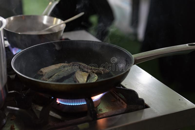 Filtrez les poissons desséchés sur une casserole chaude avec la flamme de brûleur à gaz image libre de droits