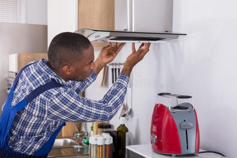 Filtro maschio africano dall'estrattore della cucina della riparazione fotografia stock