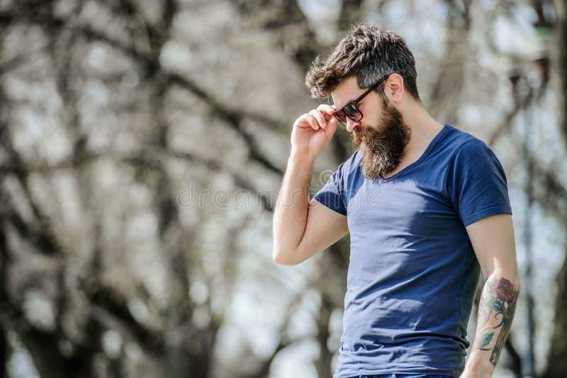 Filtro UV L'uomo brutale dei pantaloni a vita bassa barbuti indossa gli occhiali da sole protettivi Uomo barbuto con il fondo del fotografia stock