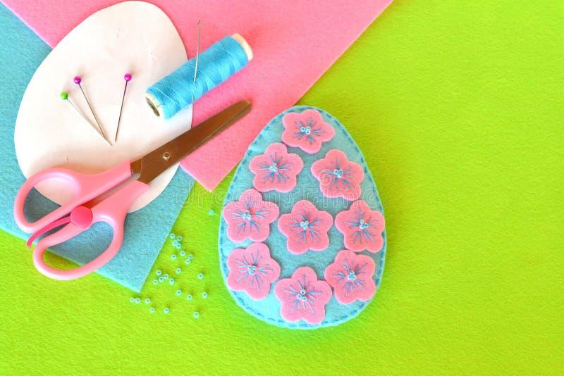 Filz-Osterei mit Blumen und Perlen Scheren, Thread, Nadel, Stifte, Papierschablonen Makro lizenzfreie stockbilder