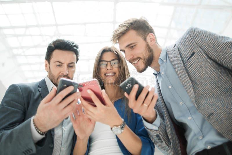 Fim acima colegas do negócio que leem SMS em seus smartphones fotografia de stock