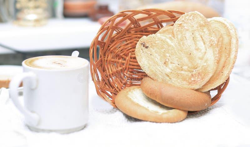 Fim acima Copo do chá e das pastelarias para o café da manhã no fundo borrado fotos de stock royalty free