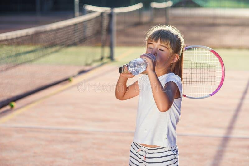 Fim acima da água potável engraçada da menina da garrafa após o treinamento duro do tênis na corte exterior no por do sol esporte fotografia de stock royalty free