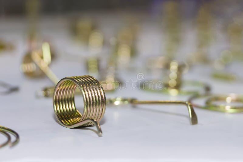 Fim acima da cor dourada brilhante da mola de bobina do metal da flexibilidade para industrial na tabela imagens de stock royalty free