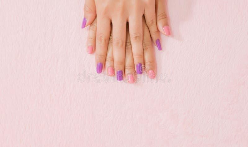 Fim acima da cor fêmea dos pregos da mão no fundo cor-de-rosa foto de stock royalty free