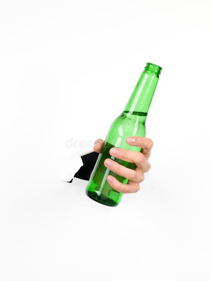 Entregue guardarar uma garrafa de cerveja através de um Livro Branco fotos de stock